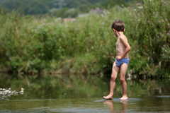 Boy walking in the water bare feet. Little boy walking by the lake, natural landscape in the country side Royalty Free Stock Photography