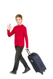 Boy walking and waving hello holding travel bag Stock Photos