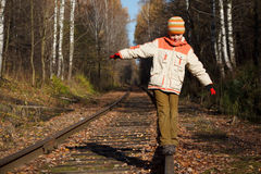Boy walks along railway in autumn in sunny day Royalty Free Stock Photo