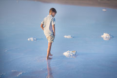 A boy walks along the shore of the lake. A Salt lake shore. A Salt Lake. A boy walks along the shore of the lake. A Salt lake shore. A Salt Lake royalty free stock photography