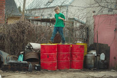 Boy walks on the barrels from oil Royalty Free Stock Photo