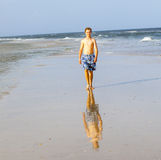 Boy walks at the beach. Handsome boy walks at the beach Royalty Free Stock Images