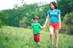 The boy walks with his mother in the meadow. A woman holds her son by the hand. The kid and mom are walking along the field. Green grass Stock Images