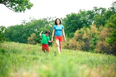 The boy walks with his mother in the meadow. A women holds her son by the hand. The kid and mom are walking along the field. Green grass Royalty Free Stock Image