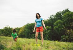 The boy walks with his mother in the meadow. A women holds her son by the hand. The kid and mom are walking along the field. Green grass Stock Images
