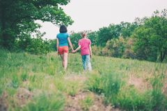 The boy walks with his mother in the meadow. A women holds her son by the hand. The kid and mom are walking along the field. Green grass Stock Photos
