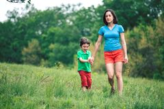 The boy walks with his mother in the meadow. A woman holds her son by the hand. The kid and mom are walking along the field. Green grass Royalty Free Stock Photos