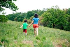 The boy walks with his mother in the meadow. A woman holds her son by the hand. The kid and mom are walking along the field. Green grass Royalty Free Stock Photo
