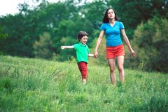 The boy walks with his mother in the meadow. A woman holds her son by the hand. The kid and mom are walking along the field. Green grass Stock Photo