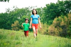 The boy walks with his mother in the meadow. A women holds her son by the hand. The kid and mom are walking along the field. Green grass Stock Photo