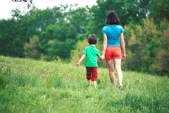 The boy walks with his mother in the meadow. A women holds her son by the hand. The kid and mom are walking along the field. Green grass Royalty Free Stock Photos