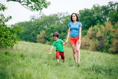 The boy walks with his mother in the meadow. A women holds her son by the hand. The kid and mom are walking along the field. Green grass Royalty Free Stock Photography