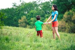 The boy walks with his mother in the meadow. A women holds her son by the hand. The kid and mom are walking along the field. Green grass Royalty Free Stock Images