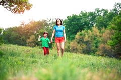 The boy walks with his mother in the meadow. A women holds her son by the hand. The kid and mom are walking along the field. Green grass Stock Image