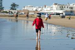 A boy walks on the ocean shore in Morocco Royalty Free Stock Photography