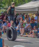 Boy walks on rolling tire in parade