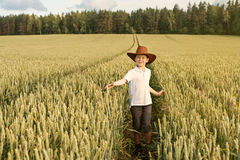 A boy walks at the wheat field in a cowboy hat royalty free stock image