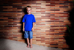 Boy on Wall. A young, stoic-looking boy standing against a brick wall Stock Image