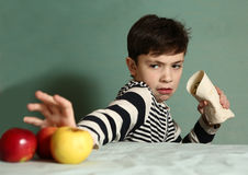Boy want to eat fast food  roll instead of apples Stock Images