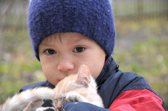 Boy in warm clothes hugging cat Royalty Free Stock Image