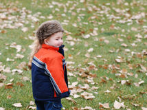 Boy in warm clothing. Young boy in warm clothing stood on grass surrounded by fallen leaves Royalty Free Stock Photo