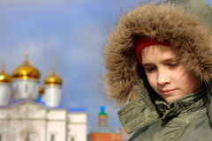 The boy in a warm hood. On a background of gold domes Royalty Free Stock Images