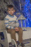 Boy in a warm sweater sitting on a sleigh Royalty Free Stock Photo
