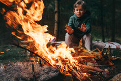 Boy warms hands near the campfire Royalty Free Stock Photo