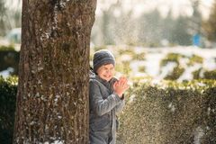 A boy warms his hands from the cold in winter.  Royalty Free Stock Photo
