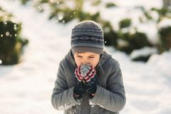 A boy warms his hands from the cold in winter.  Royalty Free Stock Image