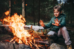 Boy warms his hands near campfire in forest Royalty Free Stock Photo