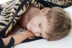 Boy warped up with counterpane Stock Images