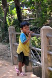 The boy was distracted by the photographer standing on the bridge. Little boy was distracted by the photographer standing on the bridge,Siem Reap, Cambodia Stock Images