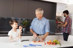 The boy was going to eat an apple while his grandfather was cooking. The man behind looks in the refrigerator. An old men in a blue shirt prepares a salad and Royalty Free Stock Photos