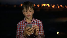The boy was lost in the night city and trying to get through the phone to his parents. Boy was lost in the night city and trying to get through the phone to his stock video footage