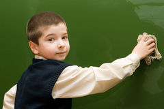 The  boy washes a blackboard Royalty Free Stock Image
