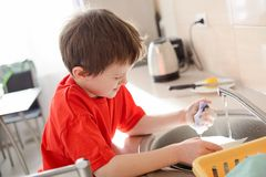Boy washes dishes in the kitchen Stock Photography