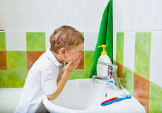 Boy washes the face. Personal hygiene. The boy washes the face Royalty Free Stock Photo