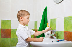 Boy washes with hand soap. Little boy in a bathroom washes with hand soap Stock Images