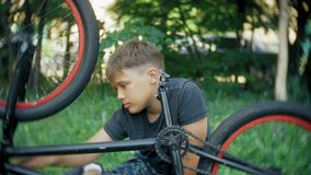 The boy washes his BMX bicycle with water and foam. 4k stock footage
