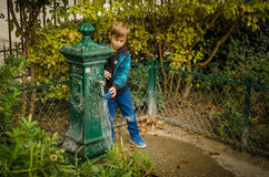 Boy washes his toy at a decorative water fountain in Paris Royalty Free Stock Images