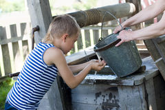 Boy washes well water. Boy washes his face with water from a well on a hot day. Russia Royalty Free Stock Photography