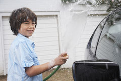 Boy Washing Car With Hose Royalty Free Stock Photos
