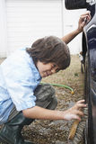 Boy Washing Car Wheel With Brush Stock Images