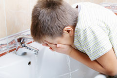 Boy washing face. In bathroom closeup photo Stock Image