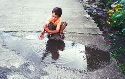 Boy washing hands in puddle. Boy washing dirty hands in puddle, 35mm film scan showing grain Stock Photos