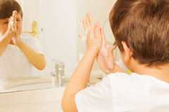 Boy washing hands with soap and looking in mirror Royalty Free Stock Photos
