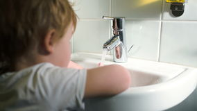 Boy washing hands with soft soap and turning off. Little boy in the bathroom washing hands with soft soap and then turning off water stock video