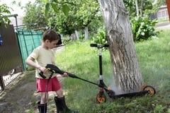 Boy washing kick scooter Stock Photos