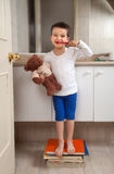 Boy washing teeth with teddy bear. Standing on some books in a abathroom royalty free stock images